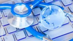 Image: Blue Stethoscope next to a blue glass globe on a blue keyboard; Copyright: panthermedia.net/Neirfys
