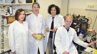 Image: The four researchers in a lab (three standing, one sitting); Copyright: Rolf Müller/UKB-UKom