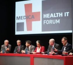 Image: Several men and woman sitting in a row on a stage. The logo of the MEDICA HEALTH IT FORUM can be seen behin them