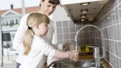 Photo: Mother and daughter in a kitchen fill a glass with water