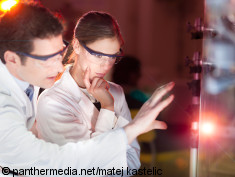 Photo: Two people look at a laser point