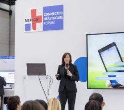 Image: A woman talks on the stage of the MEDICA CONNECTED HEALTHCARE FORUM
