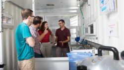 Photo: A group of people inside the lab of the sterile box in a shipping container