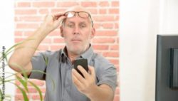 Photo: Man is trying to see something on a smartphone display