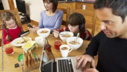 Photo: Familiy on breakfast table with mobile and laptop; Copyright: panthermedia.net/Monkeybusiness Images