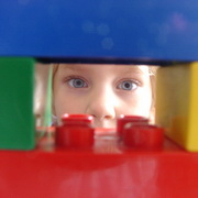 Photo: A child watches out of a Lego house