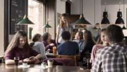 Image: view in a café with many talking teens; Copyright: Oticon