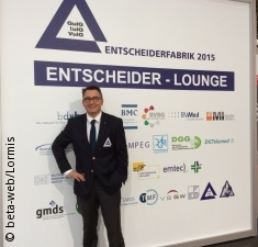 Photo: Man with a suit in front of wall with company logos