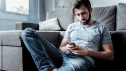 Image: Man with mobile phone sitting on the floor in front of a sofa; Copyright: panthermedia.net/yacobchuk1