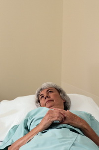 Photo: Woman lying in a hospital bed, looking thoughtfully