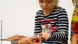 Photo: Physician takes a sample of blood from a little girl's finger