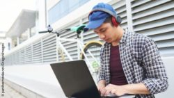 Image: A young man sitting at the curb with a laptop; Copyright: panthermedia.net/DragonImages