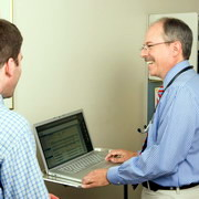 Photo: A physician in front of a laptop with a man