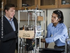 Photo: Two man standing beside a 3-D-printer