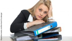 Photo: Stressed-out woman with pile of files in front of her; Copyright: panthermedia.net/Reinhard Fürstberger