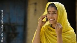 Image: Young Indian woman in yellow sari talking on mobile phone; Copyright: panthermedia.net / iphemant