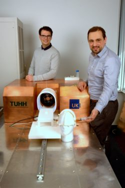 Image: Dr. Matthias Gräser (right) and Institute Director Prof. Tobias Knopp (left) stand next to the new imaging system and smile into the camera; Copyright: IBI