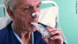 Image: Man trains his respiratory muscles with a device; Copyright: Philips GmbH
