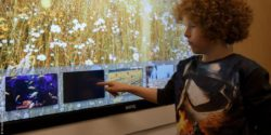 Image: Children points at a screen with different motifs; Copyright: Klinikum Dortmund/Dr. Lindel