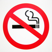Photo: Red framed rouned sign, showing a crossed cigarette