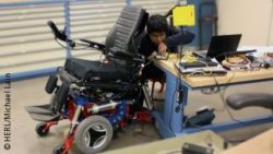 Image: Young engineer is working at a wheel chair in a lab; Copyright: HERL/Michael Lain
