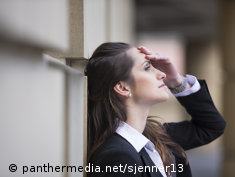 Photo: Young woman leans against a wall, tired