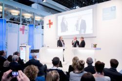 Foto: Moderator and speakers on stage of MEDICA ECON FORUM