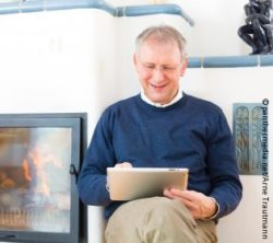 Image: Man sitting in front of fireplace and reads with Tablet; Copyright: panthermedia.net/Arne Trautmann