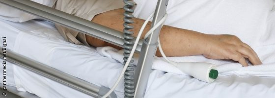 Image: Man in a hospital bed, his hand is lies next to the call button; Copyright: panthermedia.net/bignai