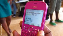 Photo: Hand is holding a colorful mobile phone; Copyright: mHealth Alliance