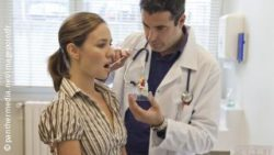 Photo: Physician takes a saliva sample from a patient