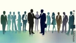 Image: A schematic picture of business people. In the center of the picture two businessmen shake hands; Copyright: panthermedia.net/scusi