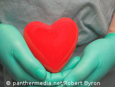 Photo: Hands with surgical gloves hold a symbolic heart