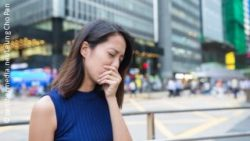 Image: Young asian women is coughing in the street; Copyright: panthermedia.net/Leung Cho Pan