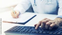 Image: blurred doctor in the background uses keyboard in the foreground and writes something on a clipboard; Copyright: panthermedia.net/Ronalds Stikans