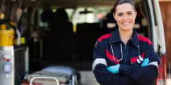 Image: Smiling female paramedic in front of an ambulance; Copyright: panthermedia.net/Michael Jung