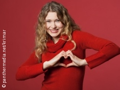 Photo: Woman shows the form of a heart with her hands