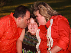 Photo: Overweight parents kiss their child
