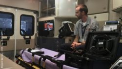 Photo: Paramedic Brett Schneider sits in an ambulance talking with a doctor via a tablet.