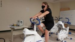 Image: woman on home-bike wears mask during training; Copyright: John Ko