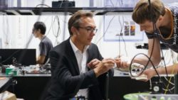 Image: Laboratory situation - Prof. Popp shows a young man a small object in his hand; Copyright: Leibniz-IPHT/Sven Döring