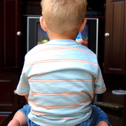 Photo: Young kid siiting in front of TV screen