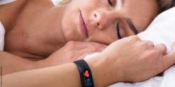 Image: A sleeping woman who is wearing a smartwatch with a heart symbol at her wrist; Copyright: panthermedia.net/Andriy Popov