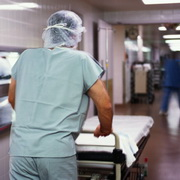 Photo: Physician pushing bed through hospital corridor