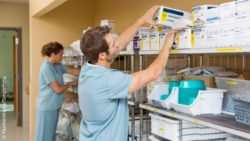 Image: Two hospital employees fill a shelf in a storage room with medical supplies; Copyright: PantherMedia/SimpleFoto