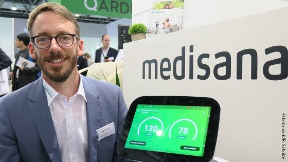 Image: Smiling man with beard and glasses at a trade fair stand next to a small robot; Copyright: beta-web/B. Scholze