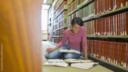 Image: Young female student is sitting between shelves on the floor of a library and reads; Copyright: panthermedia.net/Brock Jones