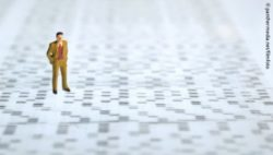 Image: A little toy figure of a man in a suit is standing on a print-out of DNA sequencing; Copyright: panthermedia.net/filmfoto