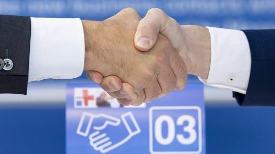 Image: Two shaking hands in front of the MEDICA Matchmaking logo
