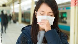 Image: A coughing woman wearing a mask; Copyright: PantherMedia/leungchopan
